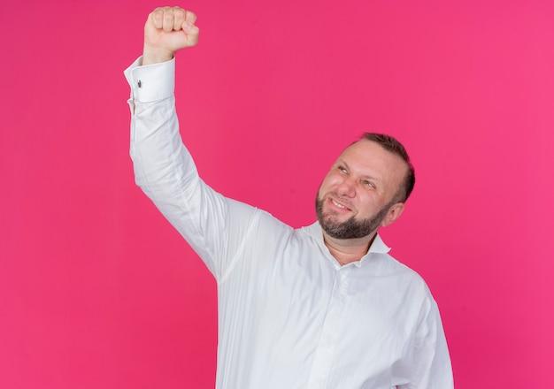 Bärtiger mann, der weißes hemd trägt geballte faust glücklich und aufgeregt freut sich über seinen erfolg über rosa wand stehend
