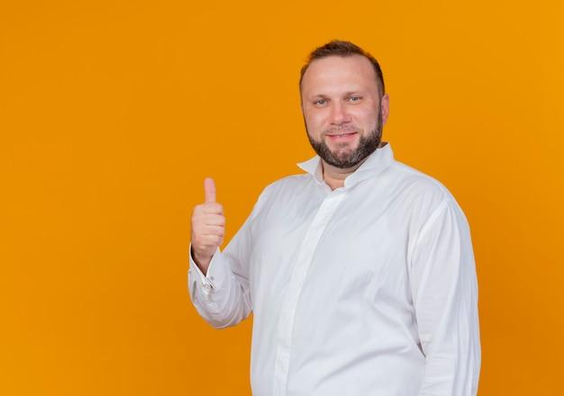 Bärtiger mann, der weißes hemd trägt lächelnd zeigt daumen hoch stehend über orange wand