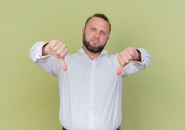 Bärtiger mann, der weißes hemd trägt, missfiel zeigt daumen nach unten stehend über lichtwand
