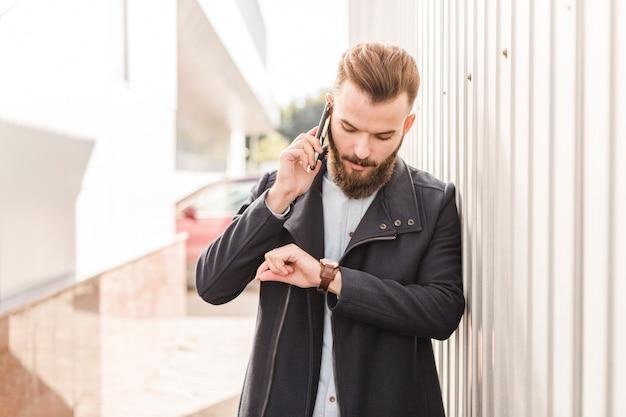 Bärtiger mann, der zeit auf armbanduhr bei der unterhaltung auf mobiltelefon betrachtet