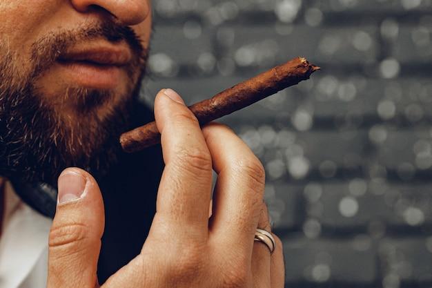 Bärtiger mann, der zigarre gegen schwarze backsteinmauer raucht