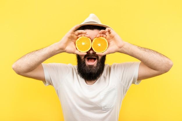 Bärtiger mann, der zwei hälften orangefarbener zitrusfrüchte in den händen hält und seine augen bedeckt