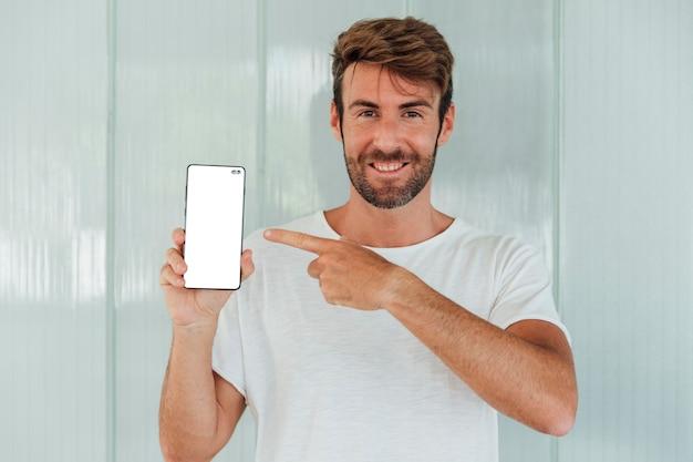 Bärtiger mann des smiley, der mobiltelefon zeigt