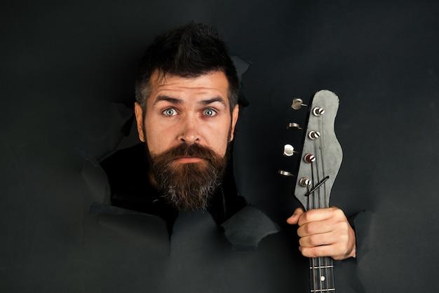 Bärtiger mann durch loch in schwarzem papier hält gitarre in der hand überraschter mann mit bart und schnurrbart