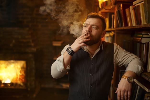 Bärtiger mann hält aschenbecher und raucht zigarette, bücherregal und reiche büroeinrichtung im hintergrund. tabakrauchkultur, spezifischer geschmack