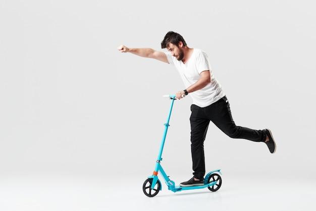 Bärtiger mann hält den elektroroller und fährt ihn, während er sich entzückt fühlt