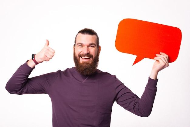 Bärtiger mann hält eine sprechblase und lächelnd zeigt einen daumen nach oben