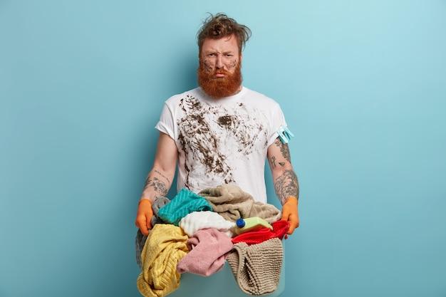 Bärtiger mann hält wäschekorb, überwältigt von hausarbeiten