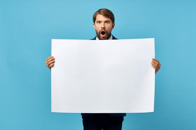 Bärtiger mann hält weiße modellplakatkopieraum blaue wand.