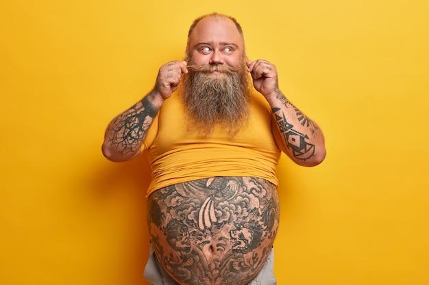 Bärtiger mann hat übergewicht, hat großen bauch und fetten bauch, lockt schnurrbart und denkt über fettabsaugung, führt sitzenden lebensstil isoliert auf gelber wand. wirkung des essens von fast food