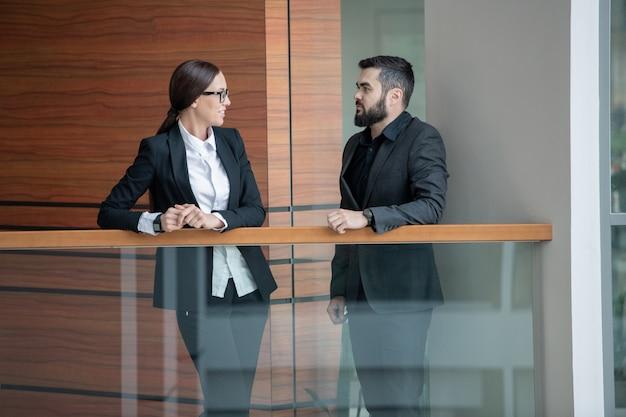 Bärtiger mann im anzug, der auf balkon im büro steht und mit kollegin in gläsern spricht