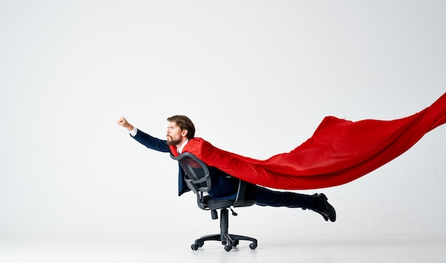Bärtiger mann im anzug reitet in einem roten superman-umhang des stuhls