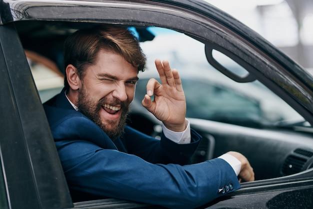 Bärtiger mann im autoanzug, der durch die stadt fährt