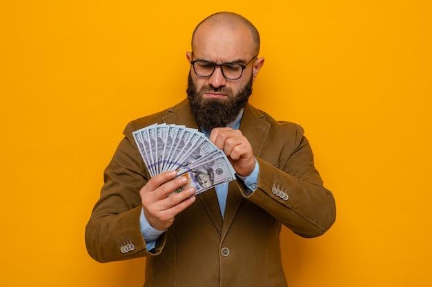 Bärtiger mann im braunen anzug mit brille, der bargeld hält und geld mit ernstem gesicht auf orangefarbenem hintergrund betrachtet