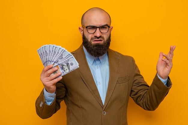 Bärtiger mann im braunen anzug mit brille, der bargeld hält und in die kamera schaut, unzufrieden, den arm vor missfallen zu heben, der über orangefarbenem hintergrund steht