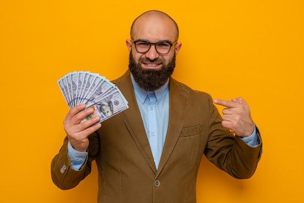 Bärtiger mann im braunen anzug mit brille, der bargeld hält und mit dem zeigefinger auf geld zeigt, fröhlich lächelnd in die kamera schaut, die über orangefarbenem hintergrund steht