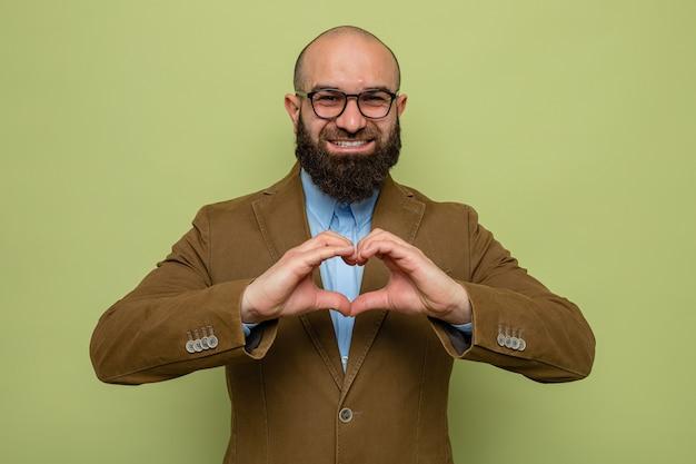 Bärtiger mann im braunen anzug mit brille, der die kamera anschaut und fröhlich lächelt und herzgeste mit den fingern auf grünem hintergrund macht