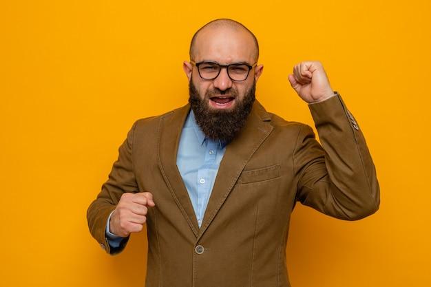 Bärtiger mann im braunen anzug mit brille, der die kamera glücklich und aufgeregt mit geballten fäusten auf orangefarbenem hintergrund betrachtet