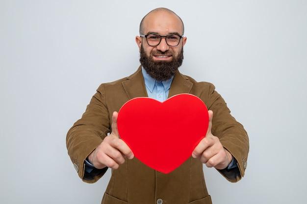 Bärtiger mann im braunen anzug mit brille, der ein herz aus pappe hält und fröhlich, glücklich und positiv lächelt