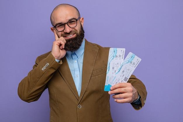 Bärtiger mann im braunen anzug mit brille, der flugtickets hält und die kamera anschaut, lächelt fröhlich glücklich und positiv auf violettem hintergrund