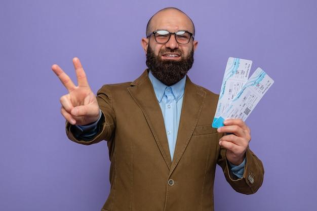 Bärtiger mann im braunen anzug mit brille, der flugtickets hält und fröhlich lächelt und ein v-zeichen zeigt