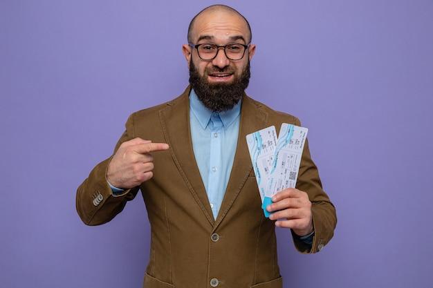 Bärtiger mann im braunen anzug mit brille, der flugtickets hält und mit dem zeigefinger auf sie zeigt, fröhlich glücklich und positiv lächelt