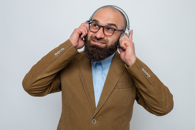 Bärtiger mann im braunen anzug mit brille und kopfhörern, die lächelnd aufblicken und seine lieblingsmusik auf weißem hintergrund genießen