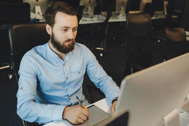 Bärtiger mann im eleganten blauen hemd, der sich auf das arbeiten mit grafiktablett und das betrachten des computermonitors konzentriert
