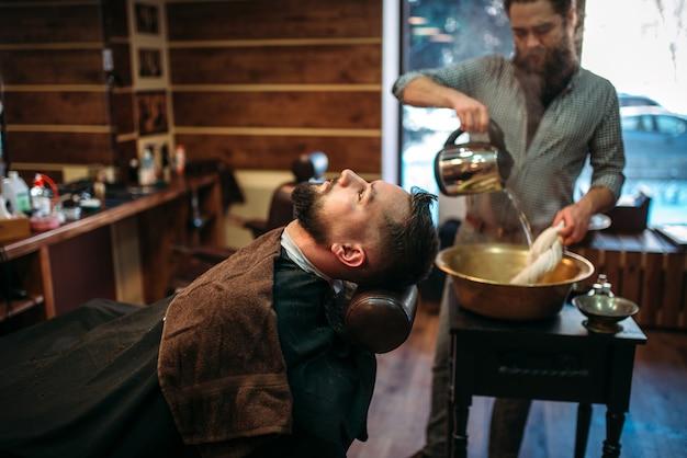 Bärtiger mann im friseursalon, friseur gießt wasser in eine kupferschale