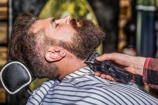 Bärtiger mann im friseursalon. mann, der friseur im friseursalon besucht. barber arbeitet mit einem bartschneider. hipster-kunde bekommt haarschnitt. hände eines friseurs mit einem bartschneider, nahaufnahme.