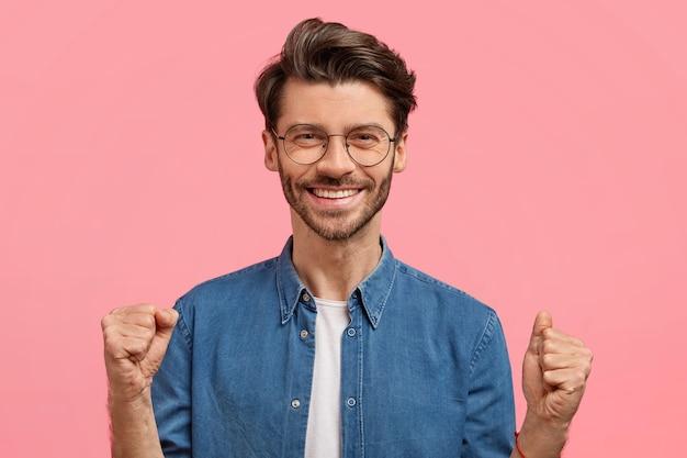 Bärtiger mann im jeanshemd und in der runden brille