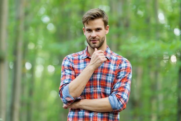 Bärtiger mann im karierten hemd mit unrasiertem gesichtsbehaarung reisen in der sommernatur, bart.