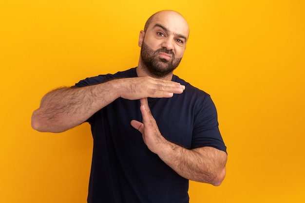 Bärtiger mann im marine-t-shirt, das auszeitgesten macht, die über der orangefarbenen wand stehen