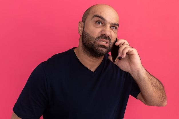 Bärtiger mann im marine-t-shirt, das genervt und gereizt schaut, während auf handy spricht, das über rosa wand steht