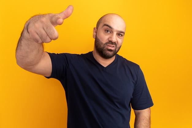 Bärtiger mann im marine-t-shirt, das verwirrt und sehr enttäuscht zeigt und mit zeigefinger zeigt, der über orange wand steht