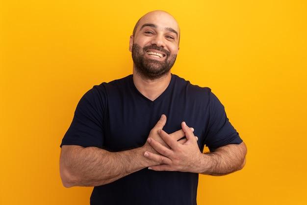 Bärtiger mann im marine-t-shirt lächelnd mit den händen auf der brust, die dankbar sind, über orange wand zu stehen