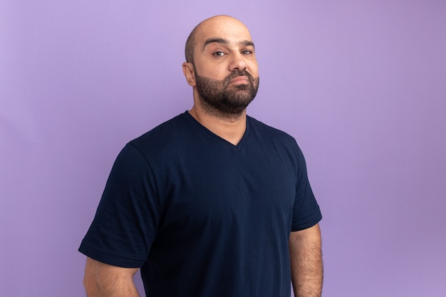 Bärtiger mann im marine-t-shirt mit ernstem gesicht, das über lila wand steht