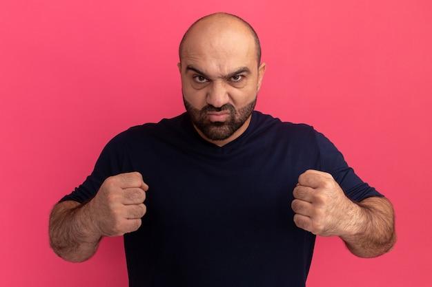 Bärtiger mann im marine-t-shirt mit ernstem wütendem gesicht mit geballten fäusten, die über rosa wand stehen