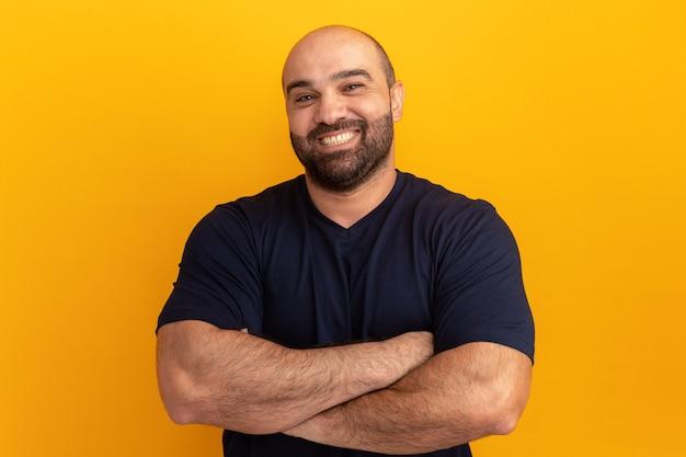 Bärtiger mann im marine-t-shirt mit lächeln auf gesicht mit verschränkten armen, die über orange wand stehen