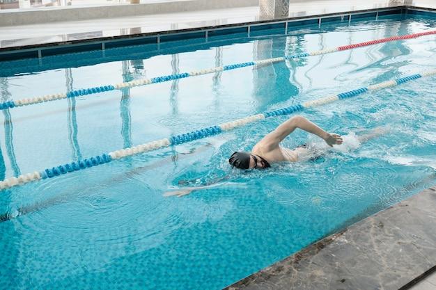 Bärtiger mann im mützen- und schutzbrillenschwimmschlag während des trainings im schwimmbad