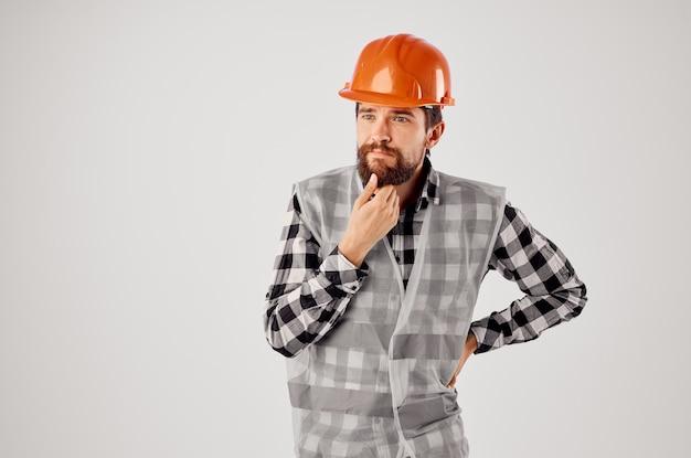 Bärtiger mann im orangefarbenen schutzhelmbau professionellen hellen hintergrund