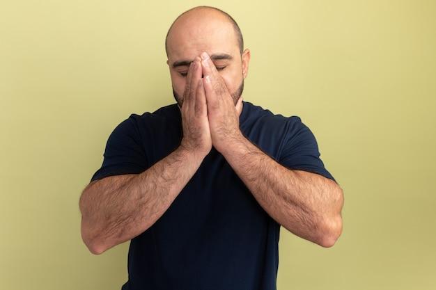 Bärtiger mann im schwarzen t-shirt, der hände zusammen auf seinem gesicht zusammenhält, deprimiert und besorgt, über grüner wand stehend