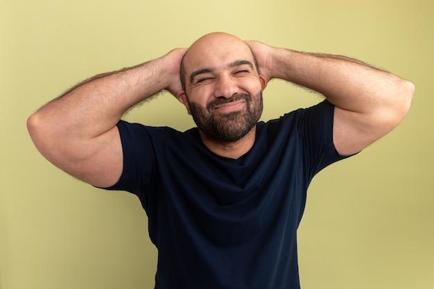 Bärtiger mann im schwarzen t-shirt, der mit den händen hinter seinem kopf über grüner wand genervt und gereizt aussieht