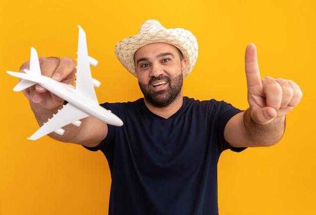 Bärtiger mann im schwarzen t-shirt und im sommerhut, der spielzeugflugzeug glücklich und fröhlich zeigt zeigefinger über orange wand steht