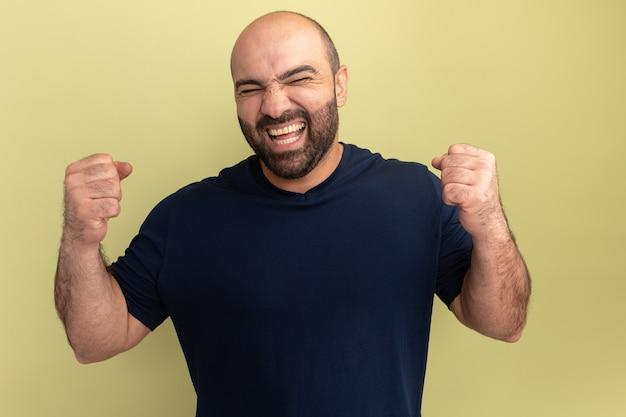 Bärtiger mann im schwarzen t-shirt verrückt glücklich und aufgeregt schreiende geballte fäuste, die sich über seinen erfolg freuen, über grüner wand zu stehen Kostenlose Fotos
