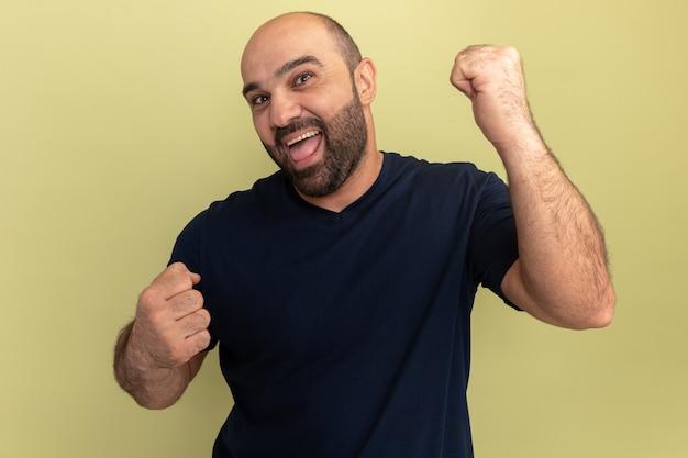 Bärtiger mann im schwarzen t-shirt verrückt glücklich und aufgeregt schreiende geballte fäuste, die über grüner wand stehen