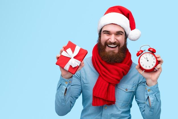 Bärtiger mann im weihnachtshut, der kleines geschenk und uhr zeigt