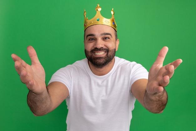 Bärtiger mann im weißen t-shirt, das die goldene krone glücklich und positiv mit den händen heraus trägt, die begrüßungsgeste machen, die über grüner wand steht
