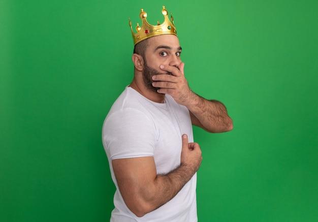 Bärtiger mann im weißen t-shirt, das die goldene krone trägt, die schockiert wird, den mund mit der hand bedeckend, die über grüner wand steht