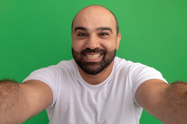 Bärtiger mann im weißen t-shirt, das freundlich lächelt und begrüßungsgeste mit den händen macht, die über grüner wand stehen